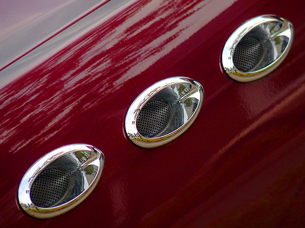 glossy, burgundy car fender with 3 chromed, reflecting, retro-looking vents running diagonally from lower left to upper right