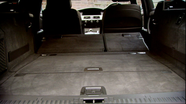 The interior of an estate car, with the back seats folded down; they do not fold down completely horizontally.