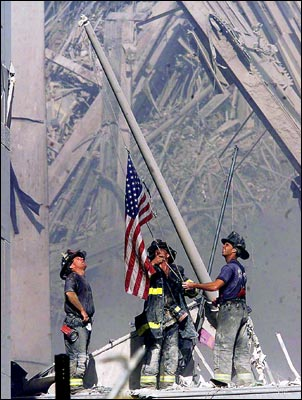Rescue workers raise the flag in front of the WTC rubble