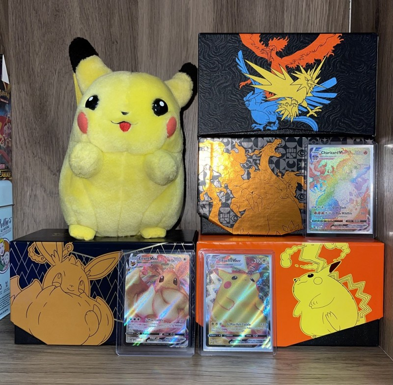 My beloved I Choose You Pikachu plush with some of my favorite Pokémon cards.