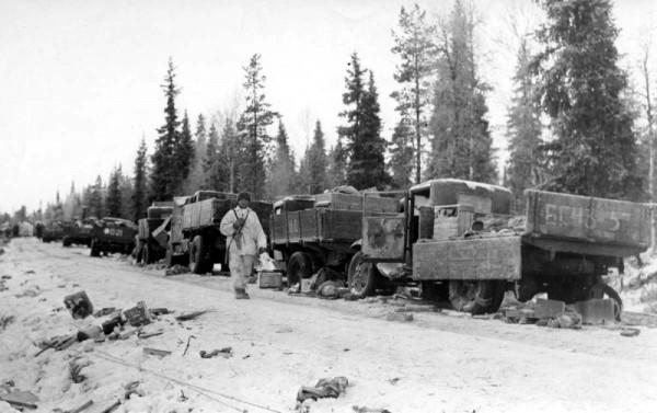 Финский солдат проходит мимо советских грузовых машин разгромленной колонны советских войск