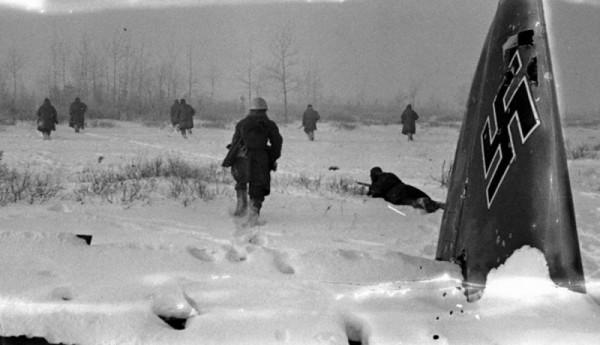 Красноармейцы Ленинградского фронта наступают на перелесок у обломков сбитого немецкого самолета