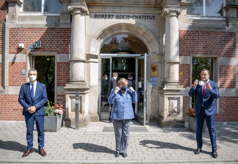 Канцлер Германии Ангела Меркель (в середине) снимает маску для фотографии перед входом в Институт имени Роберта Коха (RKI). Справа федеральный министр здравоохранения Йенс Шпан, слева президент RKI Лотар Вилер. Фото: Michael Kappeler/dpa-pool/dpa