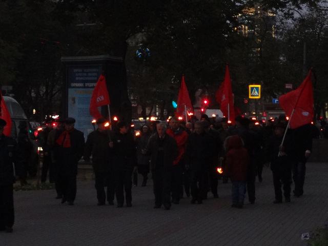 По центру города прошло не менее ста человек с факелами и красными флагами с черными траурными лентами