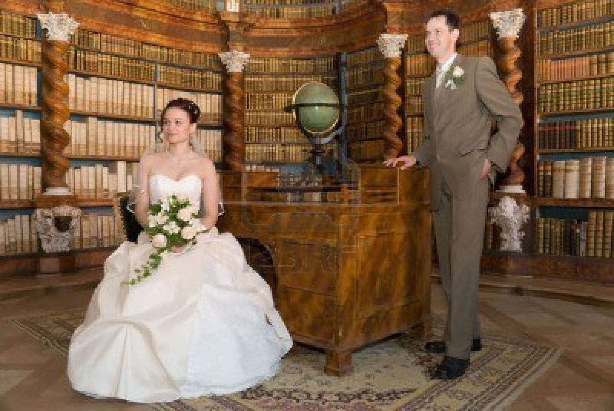 2538494-bride-and-groom-standing-in-ancient-library-with-old-globe-chair-and-wooden-shelfs-with-books