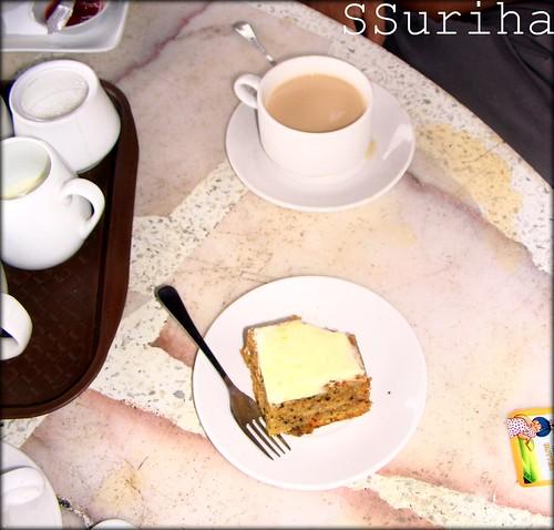 Sepiring The Bharat Tea House Carrot Cake secangkir teh panas