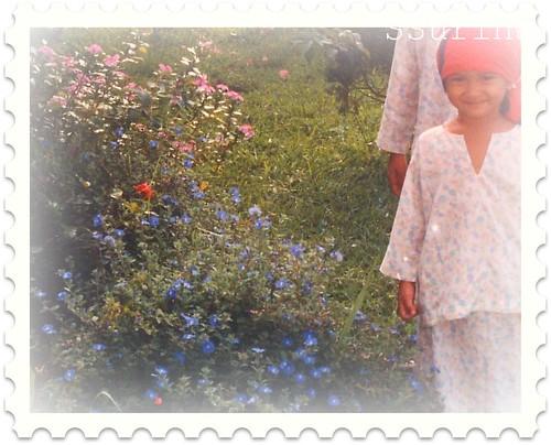 Suraya sekembali dari mengaji posing tepi bunga ungu biru Kota Kinabalu