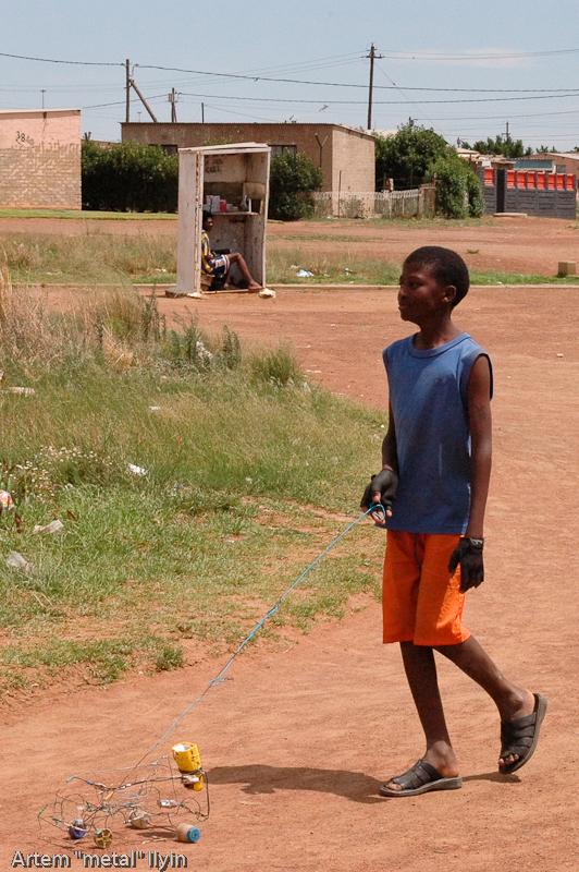 Мальчик с самодельной игрушкой в бедном пригороде Йоханнесбурга, Южная Африка