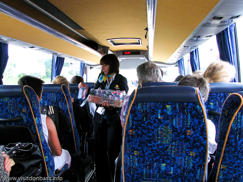 Стюардесса Luxair раздает пассажирам в автобусе сухой паек: бутерброды и минеральная вода
