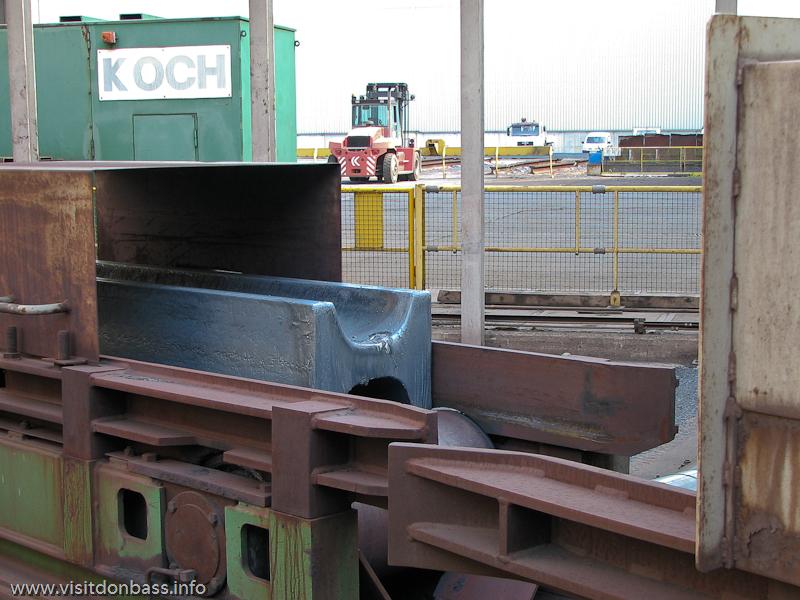 Стальная заготовка транспортируется в прокатный цех. Крупный план. Металлургический завод ArcelorMittal Esch-Belval в Люксембурге