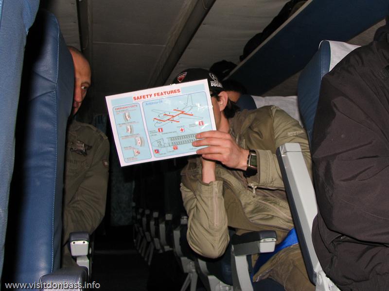 Аэропорт Черновцы. Внутри самолета Ан-24 Air Urga UR-ELN пассажиры изучают схему эвакуации
