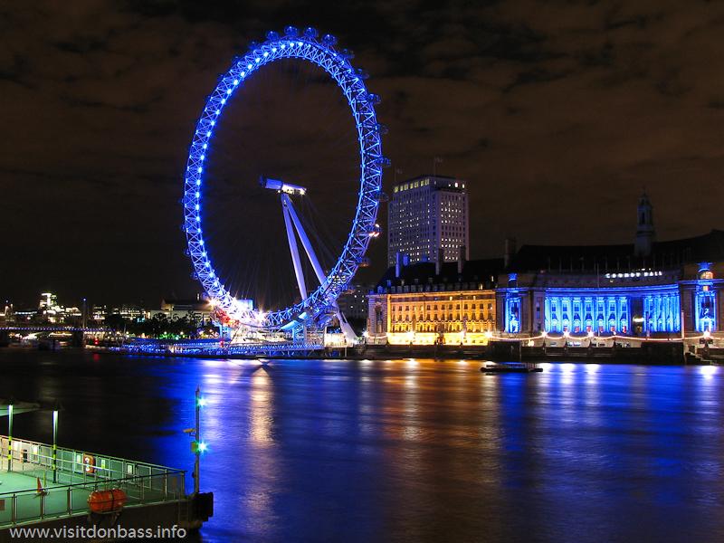 Открыточный вид на колесо обозрения London Eye, стоящее на берегу Темзы в центре Лондона