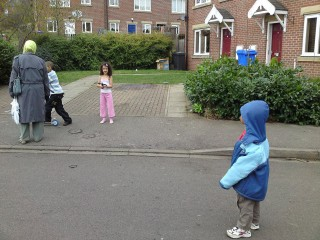 Greeting some kids playing outside. Notice the girl's simple dressing (it was still winter!) compared to our own.