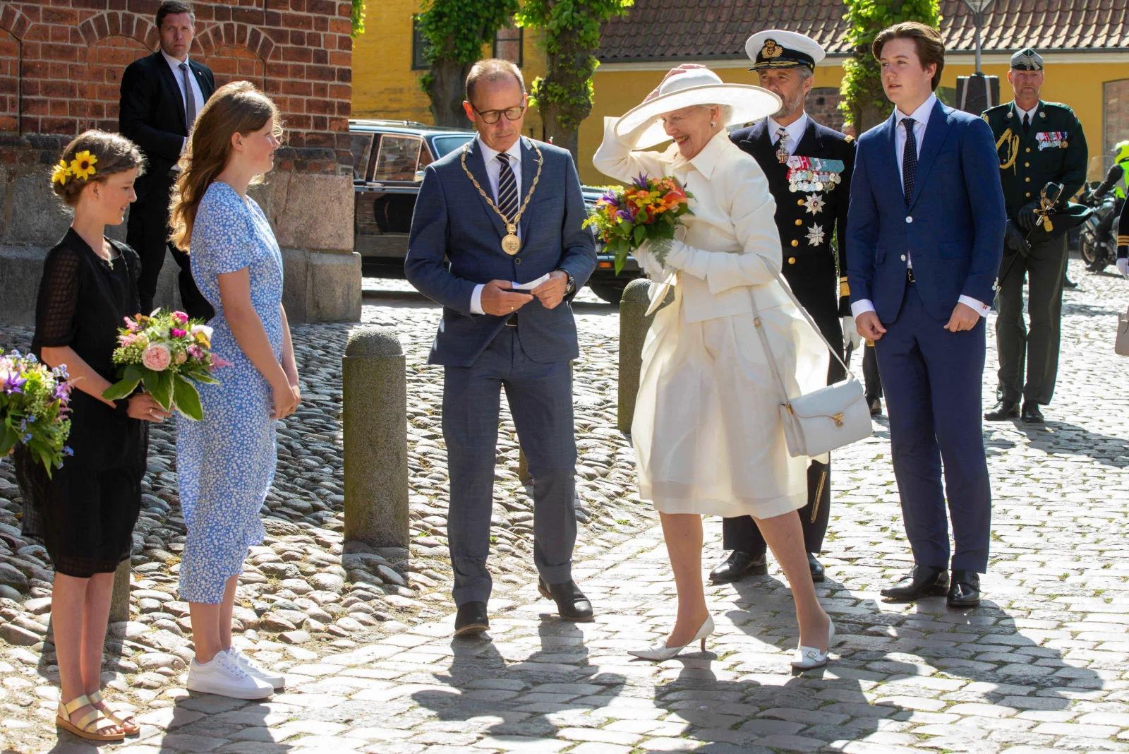Королева Маргрете спасает шляпу от внезапно налетевшего ветра)...