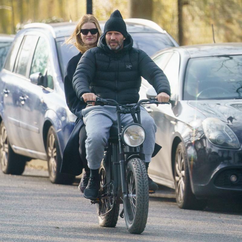 Британская 33-летняя супермодель Роузи Хантингтон-Уайтли и английский 53-летний актёр Джейсон Стейтем катаются на электрическом велосипеде в Лондоне (24.03.2021)