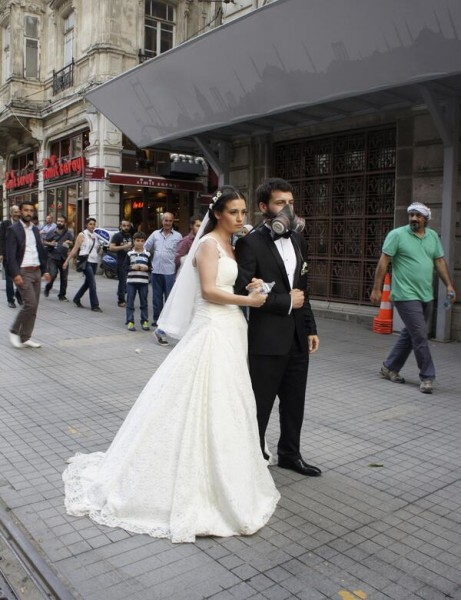 A couple in wedding garb poses not far from the protests
