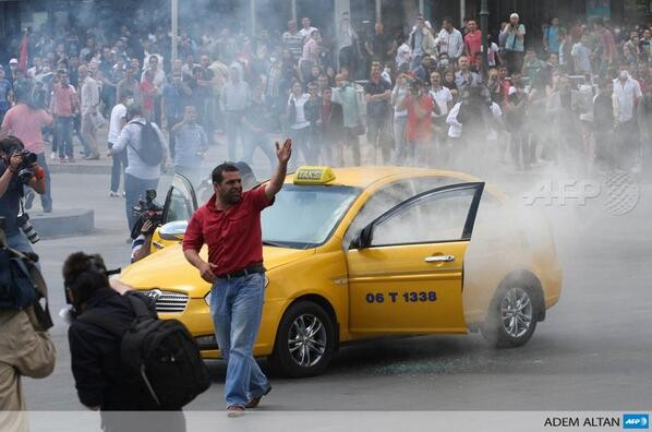 A taxi driver shouts at police after a gas canister hit his car during clashes in Ankara