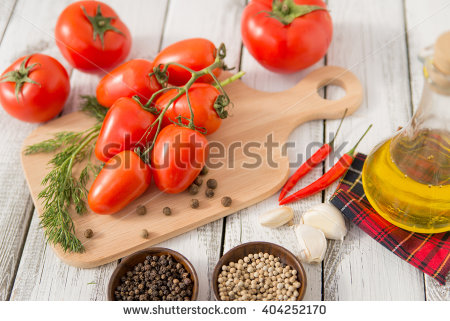 stock-photo-close-up-of-fresh-red-delicious-tomatoes-with-greenery-on-an-old-wooden-background-404252170