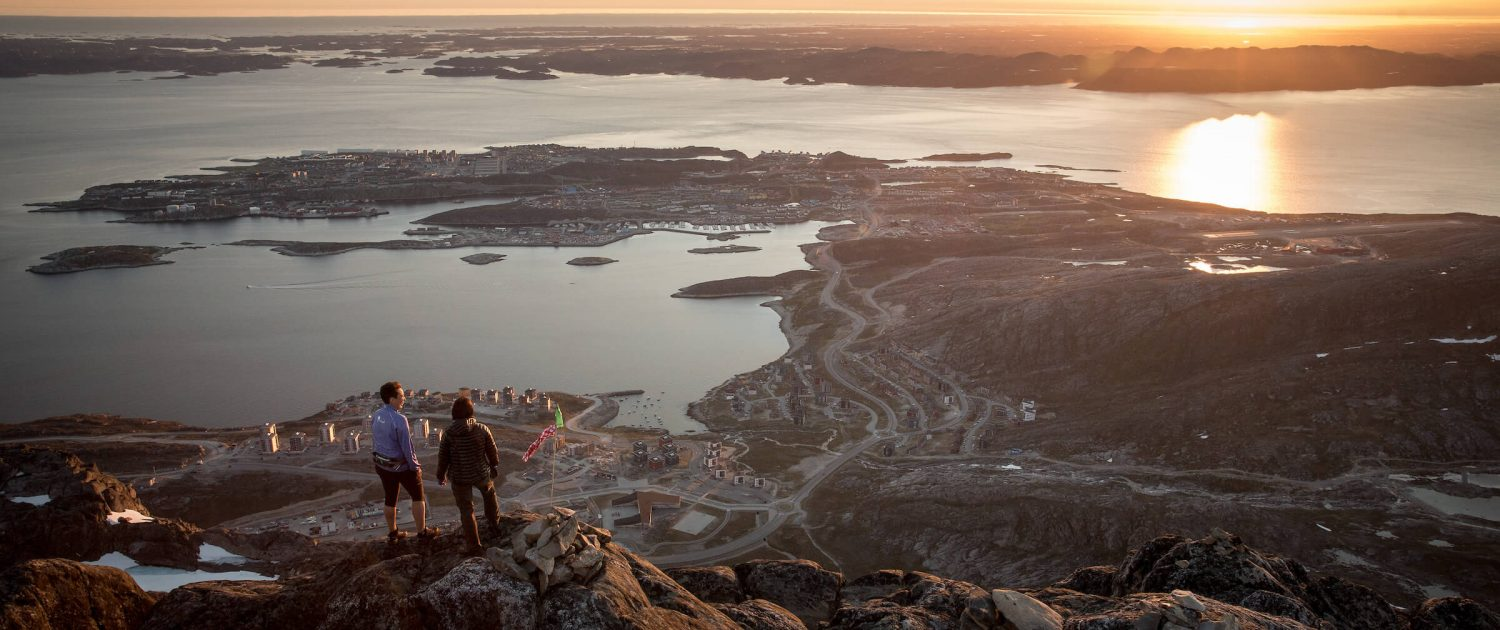 two-hikers-overlooking-nuuk-in-the-midnight-sun-from-the-peak-of-ukkusissaq-store-malene-in-greenland-1-1500x630