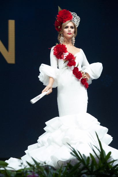 Spain an iconic traditional robe, with white meaning purity and a ripple of red carnations.jpg