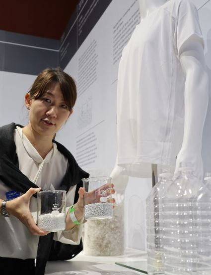1   A woman shows material made from recycled plastic bottles developed by Uniqlo and Toray, and a T-shirt, in London on Monday..JPG