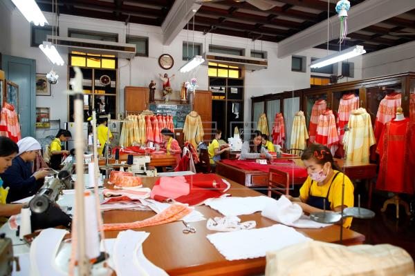 3  Tailors work on preparing embroidered silk robes for Pope Francis ahead of his upcoming visit to Thailand, at the Sacred Heart Convent School in B…