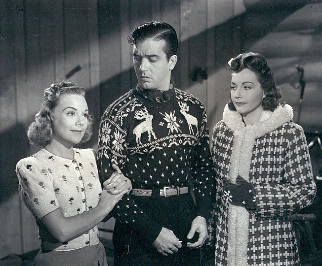 3    Sonja Henie and Lynn Bari flank John Payne in his ski sweater..jpg