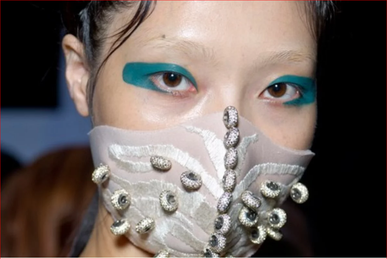_Chinese designer Masha Ma has joined models, in launching versions of the face mask. She embedded her SS15 collection with Swarovski crystals and pr…