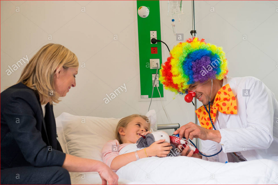 Male doctor wearing clown costume making girl patient smile in hospital bed  2014.PNG