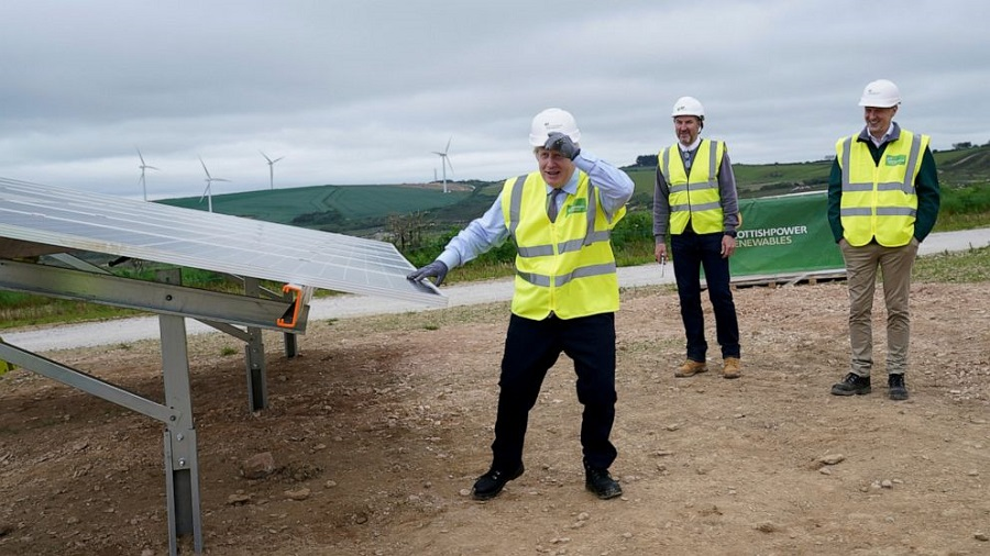 British Prime Minister Boris Johnson, left, stands next to a solar panel as he visits the Scottish Power Carland Cross Windfarm in Newquay, Cornwall,…