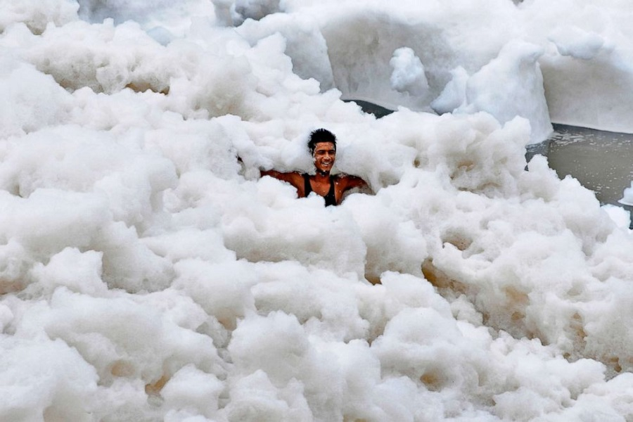 _900 x 600 A man immerses himself in a large amount of toxic foam formed along the banks of the Yamuna.jpg