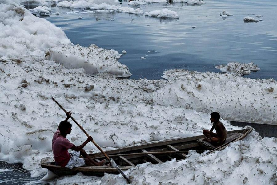 _900 x 600 Boys sit in a boat before immersing an idol of Hindu god Lord Ganesh in the polluted Yamuna ri.jpg