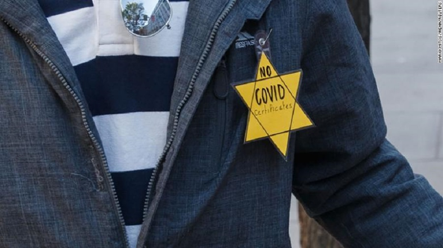 4 A protester wears a yellow Star of David with No Covid certificates printed on it while marching in London for the Unite for Freedom anti-lockdown …