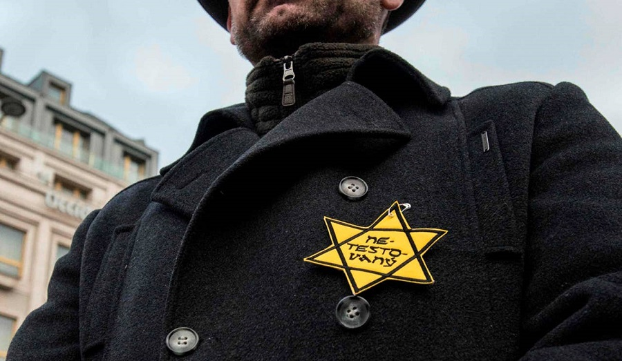 A man with a Nazi like star of David reading 'untested' takes part in a protest in Prague, January 8, 2021. January.jpg