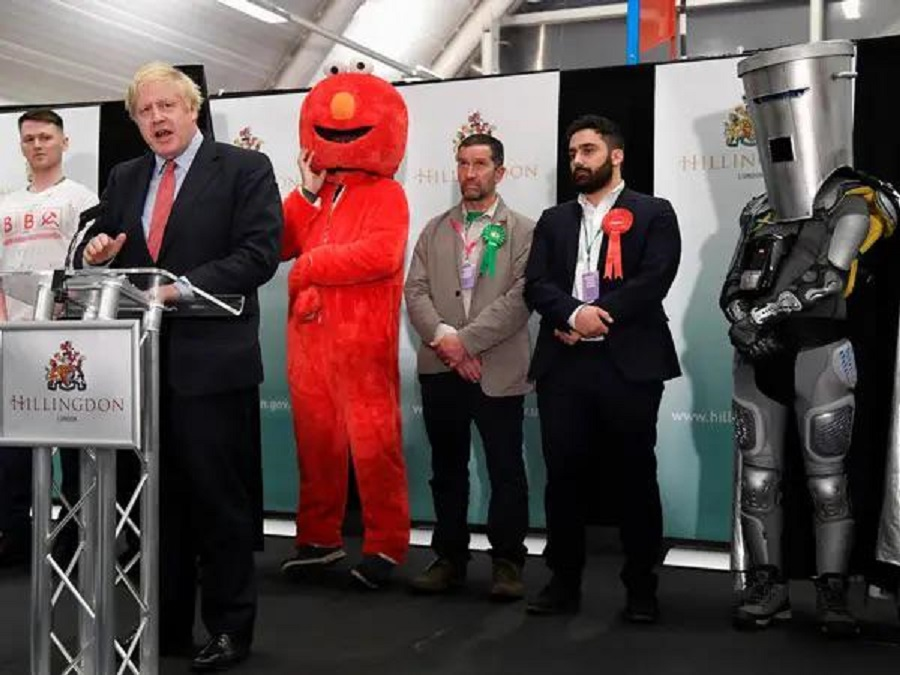 12 Elmo and Lord Buckethead are standing behind him, and yet Alexander Boris de Pfeffel Johnson is still the biggest muppet in this picture.jpg