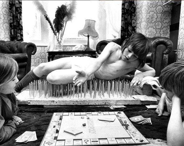 8-летний мальчик по имени Марк лежит на кровати из гвоздей, играя в «Монополию», Лондон, 1976 год