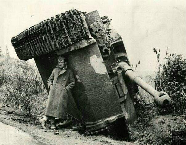 Британский солдат прячется от дождя под перевёрнутым танком «Тигр», Италия, 1944 год