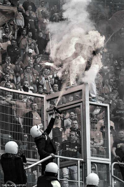 Работник службы безопасности на стадионе использовал перцовый спрей против фаната, держащего фаер в руке