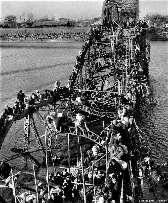 Жители Пхеньяна спасаются бегством из осаждённого города по опорам разрушенного моста. Корейская война, октябрь 1950 г.