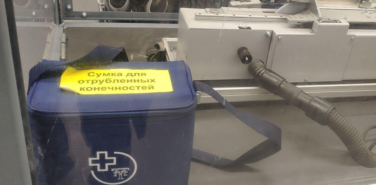 Сумка стоит рядом с аппаратом для заточки коньков