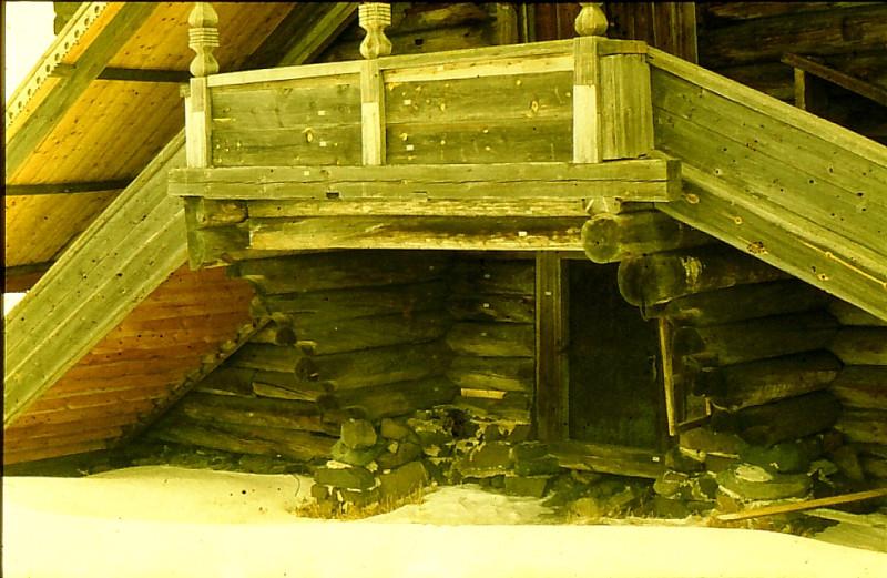Столбы крыльца работы 1950-х годов, восстановленные в 1990-х. Заменены подгнившие пятки столбов, хотя экономически плотникам было бы выгодней изготовить новые по реставрационным расценкам. Но из уважения к старшему поколению, которое навыки плотницкого ремесла приобретали из рук в руки,а не по книгам, выполнили лишь протезы на сгнивших участках. Внизу дверь в подклет, обитая железом. Виден фрагмент фундамента на известковом растворе 1860-х.