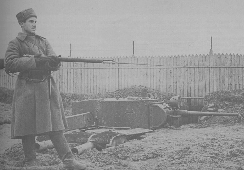 Неисправный танк БТ-5, врытый в землю в пригороде Москвы, и боец народного ополчения