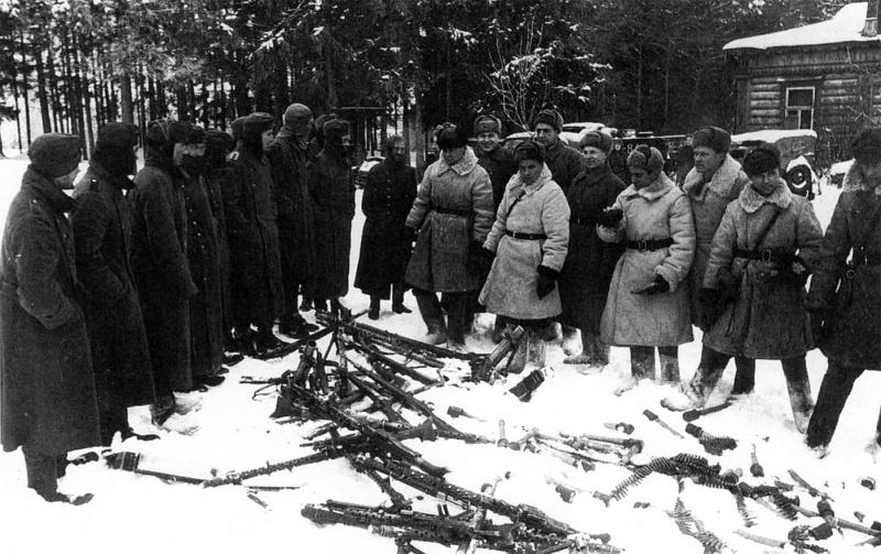 Русские офицеры осматривают трофейное оружие перед строем пленных немецких солдат. Битва за Москву.