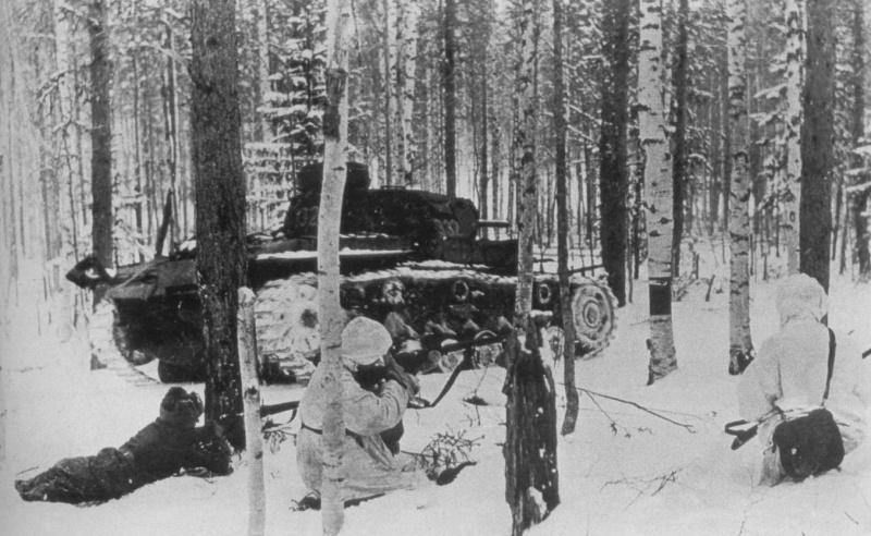 Советские солдаты в бою в лесу под Москвой. двое вооружены винтовками Мосина, у третьего сумка с дисками к пулемету ДП. Танк — подбитый немецкий танк Pz.Kpfw. III.