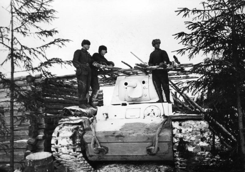 Советские танкисты у замаскированного танка КВ-1 из состава 4-й танковой бригады в одной из подмосковных деревень.