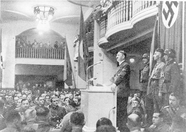 """Адольф Гитлер незадолго до взрыва бомбы во время своего выступления в """"Бюргербройкеллере""""."""