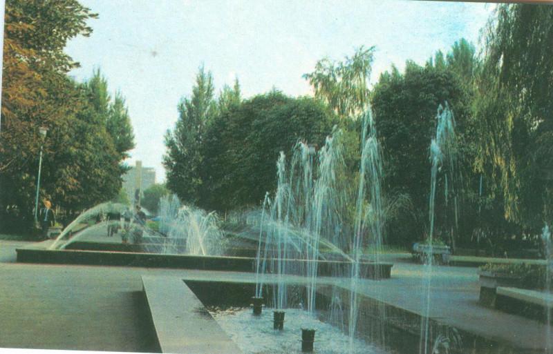 фонтан на площади Героев Великой Отечественной Войны. фотооткрытка 1990. сохранился, переживал реконструкцию. летом работает. на фото вдалеке видно здание, где проектировали теплицы