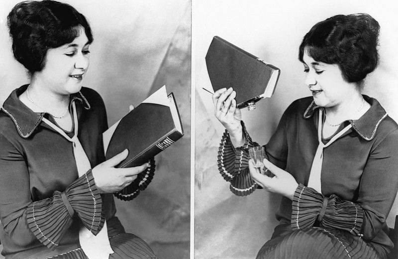 Дама демонстрирует, как можно спрятать в книге бутылочку виски.. 1927 год