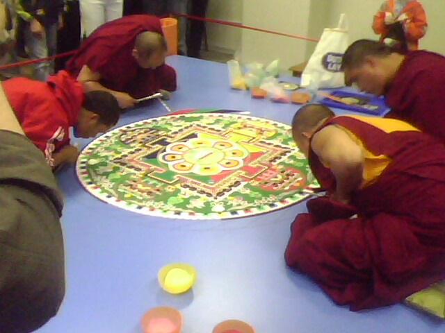 монахи стоят мандалу