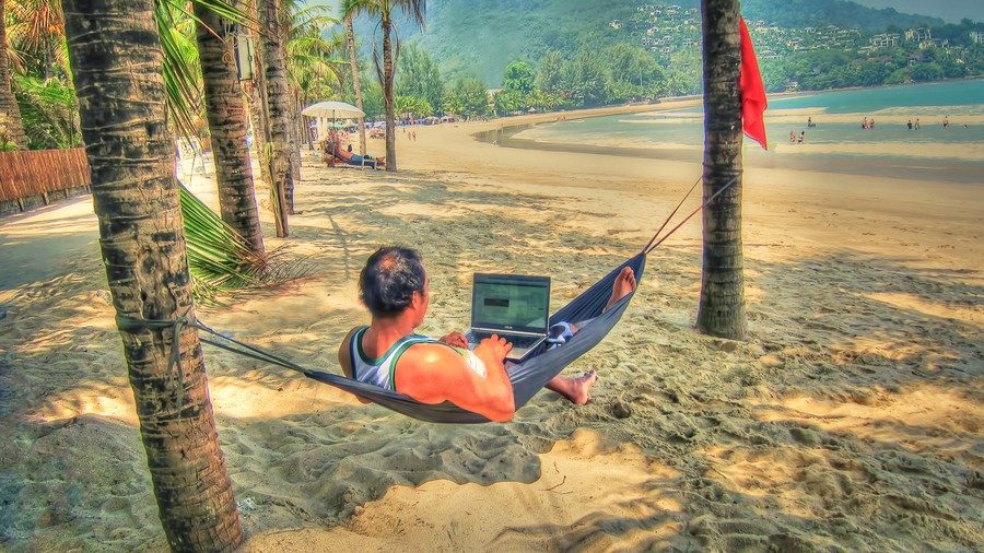 Captain-Kimo-at-the-Beach-in-Phuket-Thailand-Working-on-Monthly-Newsletter
